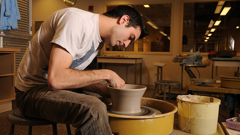 An 国家 student sculpts pottery at the 工艺 中央.