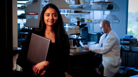 A young NC State STEM student stands in the foreground with a researcher in a lab coat behind her.