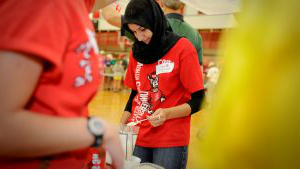 An NC State student hard at work spooning out rice at a service event.