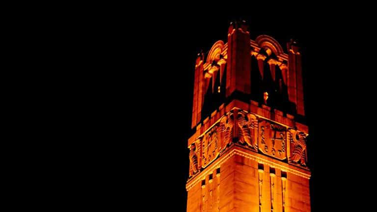 The NC State Memorial Bell Tower, lit orange from below.