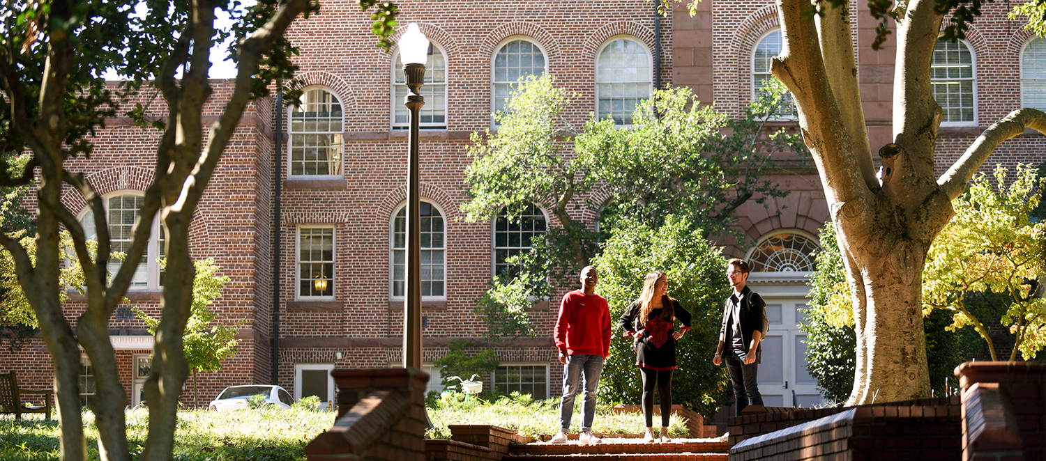 Three NC State students bathed in afternoon light outside Holladay Hall.