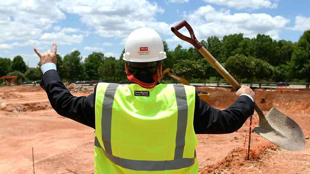 "A man wearing a ""College of Agriculture and Life Sciences"" hard hat and holding a shovel stands in front of a pit of dirt"